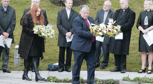Kat Wilkinson, whose brother Aiden Gallagher was killed, and Stanley McComb, whose wife Ann was killed, lay some flowers during the remembrance service for the victims of the Omagh bomb