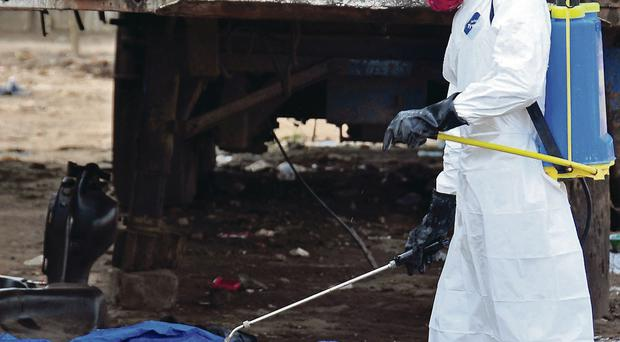 The body of a man who is suspected of dying from the Ebola virus is sprayed with disinfectant in the Liberian capital Monrovia