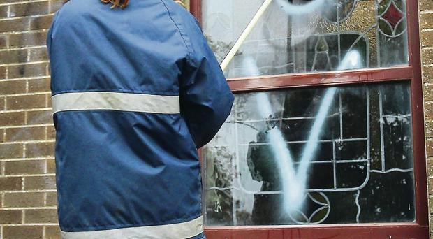A resident cleans graffiti off the church window yesterday