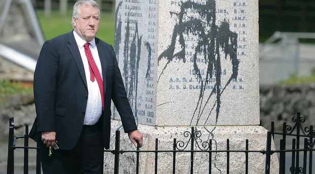 SDLP councillor Pat Catney examines the damage caused to the war memorial in Glenavy by the paint attack