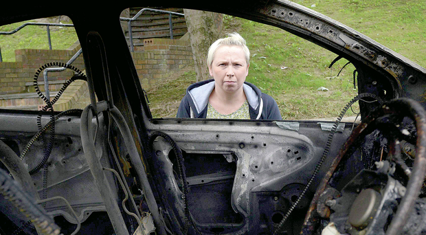 Leeanne Marshall looks at the damage caused after an arson attack on her and her daughter's car