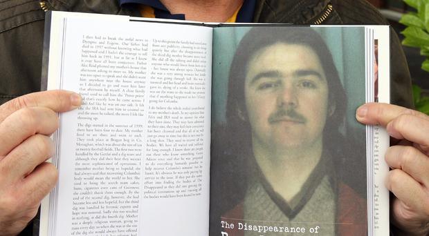 Kieran Megraw holds a book with a picture of his brother Brendan Megraw, one of the so-called Disappeared