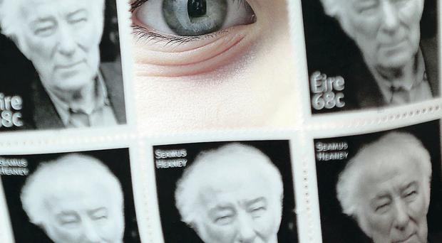 Seamus Heaney's granddaughter Aibhin (6) peers through the set of stamps yesterday