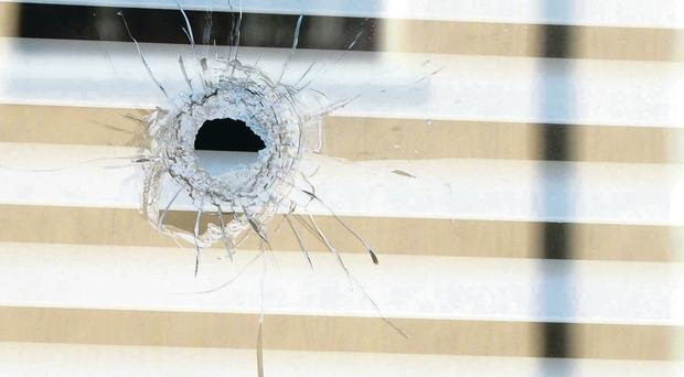 A bullet hole in the window and the smashed front door