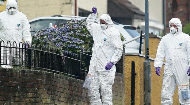 Forensic officers examine the scene of the shooting in north Belfast