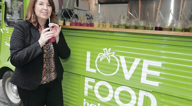 Belfast Telegraph reporter Joanne Sweeney samples the drink made from leftover fruit and vegetables at Victoria Square yesterday