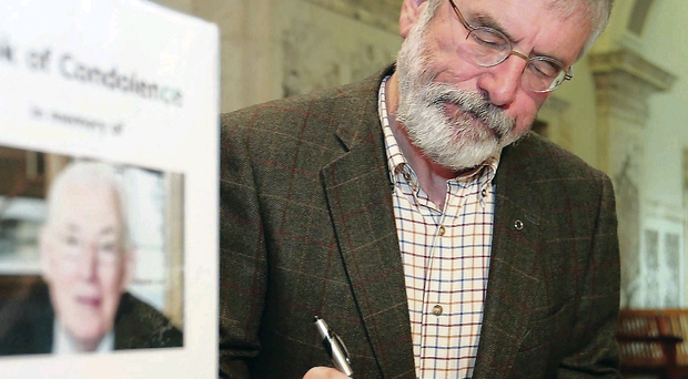 Sinn Fein's Gerry Adams signs the book of condolence in the Great Hall at Parliament Buildings, Stormont
