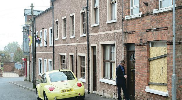 DUP councillor Brian Kingston calls at the house in Woodvale that was targeted by racists