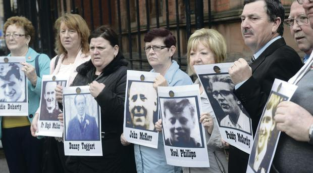 Family members of those killed during the Ballymurphy Massacre protest at a preliminary inquest in Belfast yesterday