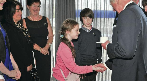 The Prince of Wales meets nine-year-old Sophie Greene, the daughter of PSNI Constable Declan Greene, who was killed on duty in 2008