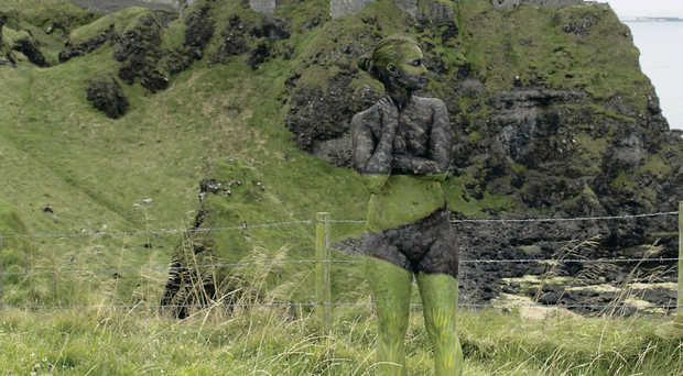 A female model is body painted into the foreground of Dunluce Castle