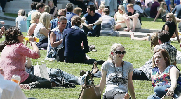 People soaking up the sun at Belfast City Hall