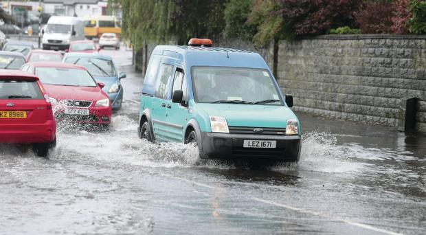Vehicles negotiate flood water on the Falls Road