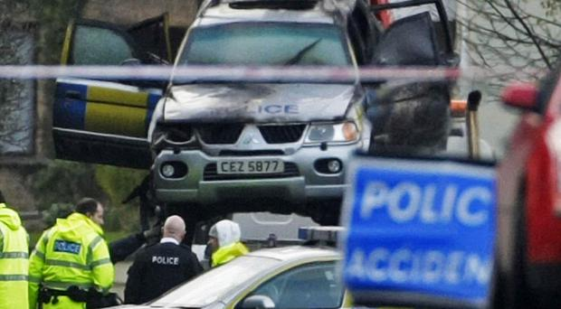 The police vehicle in which the four officers died is removed from the crash scene after the fatal accident