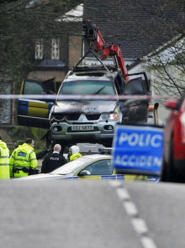 The remains of the vehicle in which the four constables died are removed from the crash scene