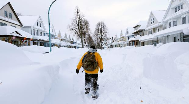 A pedestrian is dwarfed by 5ft high snowdrifts in south Buffalo, New York, yesterday