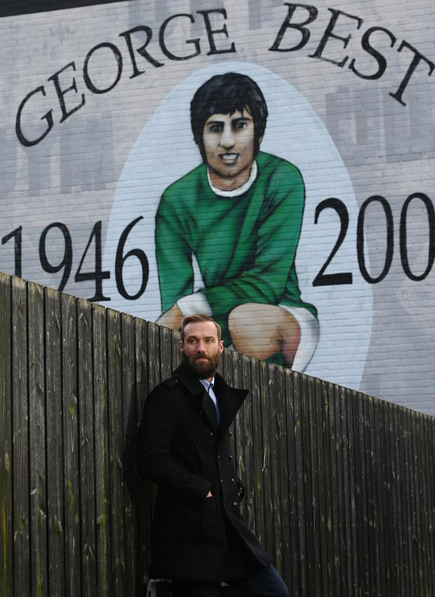 Calum Best beside the mural of his father