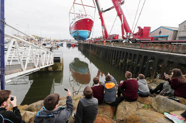 The Steadfast is lifted by a huge crane watched by a large crowd at Kilkeel harbour and is finally lowered into the water