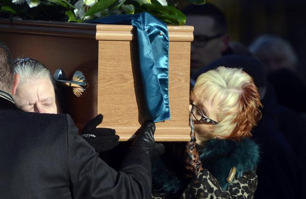 Eileen kisses her sister Una Crudden's coffin following Requiem Mass at the Church of the Nativity in Poleglass