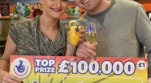 Lauren McLarnon celebrates with her partner Michael Mullen after she won £100,000 on a National Lottery scratchcard at her local shopping centre