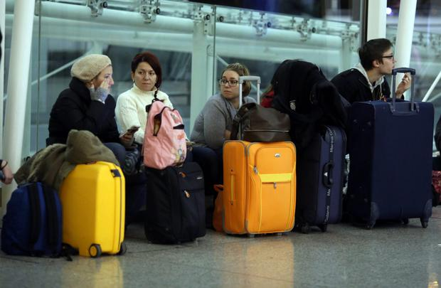 People wait at Stansted Airport after dozens of flights were cancelled or delayed yesterday