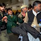 Volunteers at a hospital carry a student injured at the school attacked by Taliban gunmen