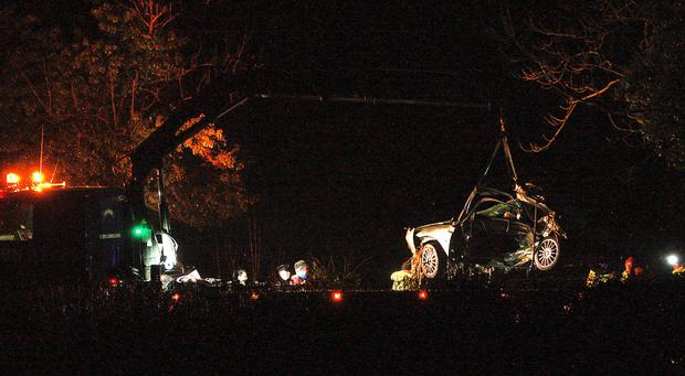 Damaged car is lifted away from the crash scene last night