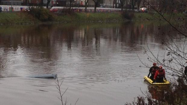 Rescue workers at the scene on the River Lagan yesterday where a van went through the railings and into the water