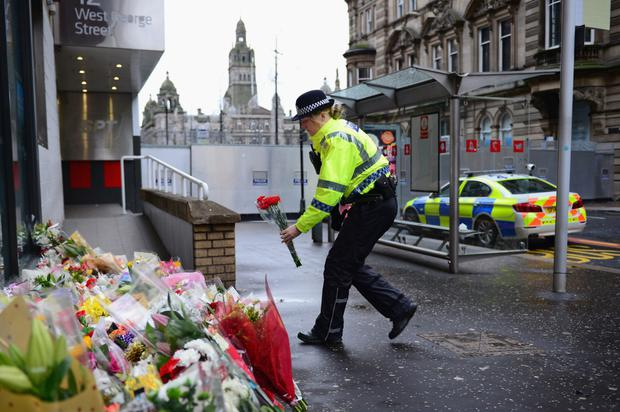 Police officer lays floral tributes near to the crash scene yesterday