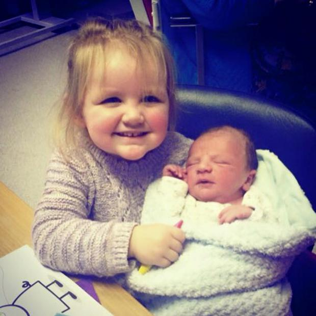 Lucy Evangelista's daughter Leila holds her new brother Luke James McCullough