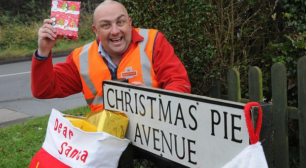 Postman Trevor Meadwell next to a festive street sign for Christmas Pie Avenue in Guildford.