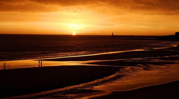 The calm before the storm as people walk on the beach near Tynemouth at sunrise
