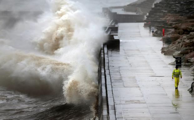 Waves crash against the sea wall in Blackpool as high winds batter the north of the UK
