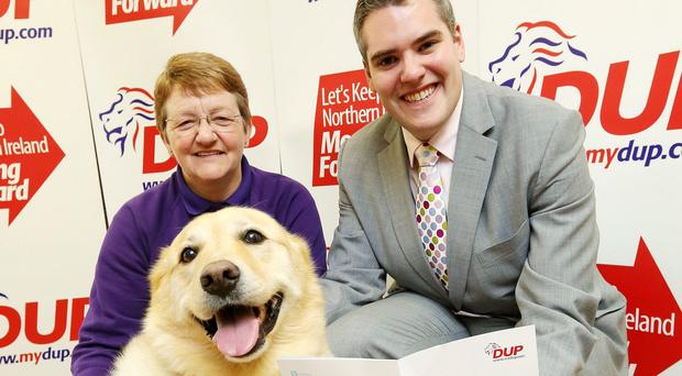 Gavin Robinson with Heather Oliver, Assisi Animal Sanctuary manager and rescue dog Sophie in Newtownards (Kelvin Boyes/Press Eye/PA)
