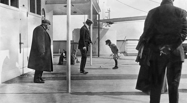 Robert Douglas Spedden, watched by his father Frederic, playing with a spinning top on the deck of the Titanic