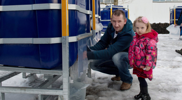 Ciaran McElduff and his daughter Amiee-Rose visit the temporary water station in Loughmacrory to fill up