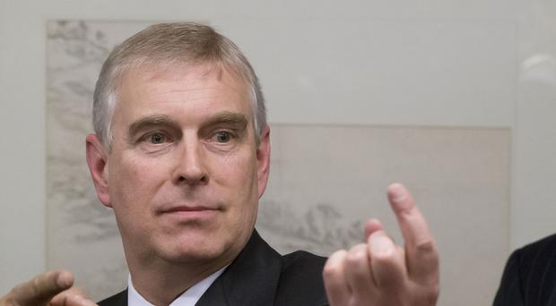 The Duke of York gestures as he speaks with business leaders during a reception on the sidelines of the World Economic Forum in Davos.
