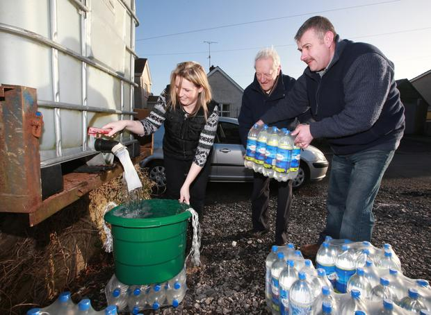Crisis: Donald Crawford (right), helping Judith Moutray and Edwin Fletcher to fresh water in Lisbellaw this week