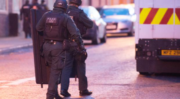 Police officers carrying armoured shields at the scene yesterday in John Street, Derry, where a man barricaded himself into a room in the Meridian Apartments