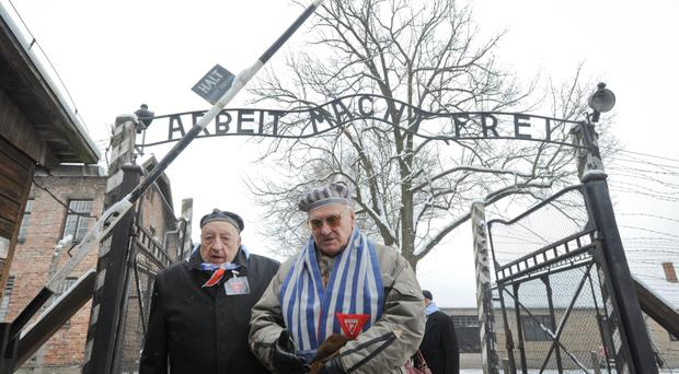 Holocaust survivors walk through the gate of Auschwitz Nazi death camp yesterday