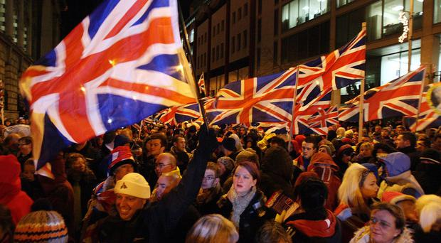 Loyalist protesters carrying Union flags block the back of the City Hall in Belfast