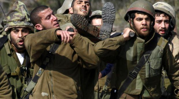 Israeli soldiers carry an injured colleague yesterday after the missile attack