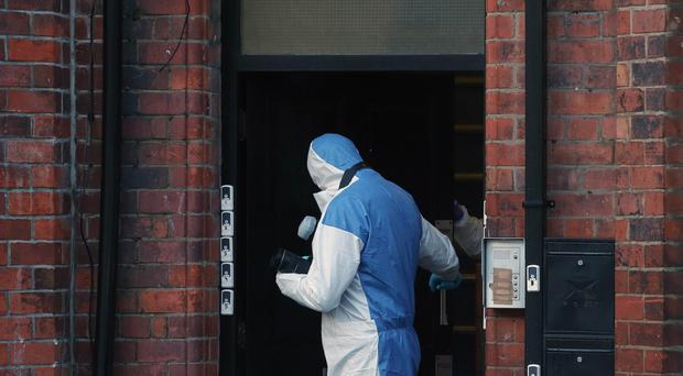 A forensic officer examines the sealed-off house in India Street