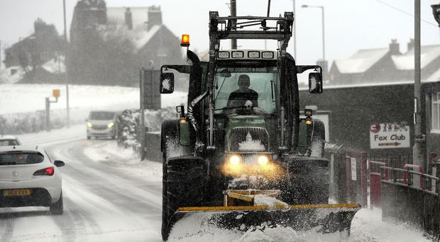 A snowplough clears the road between Bradford and Halifax as schools and transport were disrupted after heavy snow hit parts of the country