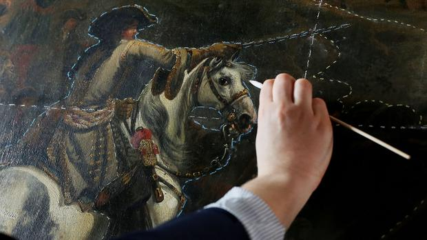 Pearl O'Sullivan uses a swab during the conservation of Jan Wyck's painting,The Battle of the Boyne at Malahide Castle in Dublin