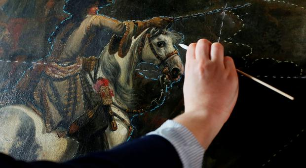 Pearl O'Sullivan uses a swab during the conservation of Jan Wyck's painting,The Battle of the Boyne, at Malahide Castle in Dublin yesterday