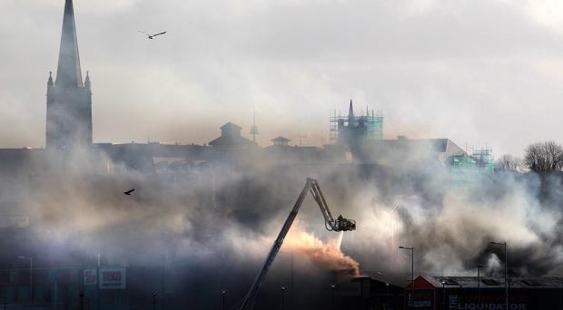 Fire crews use an aerial crane in an attempt to bring the fire in Londonderry under control