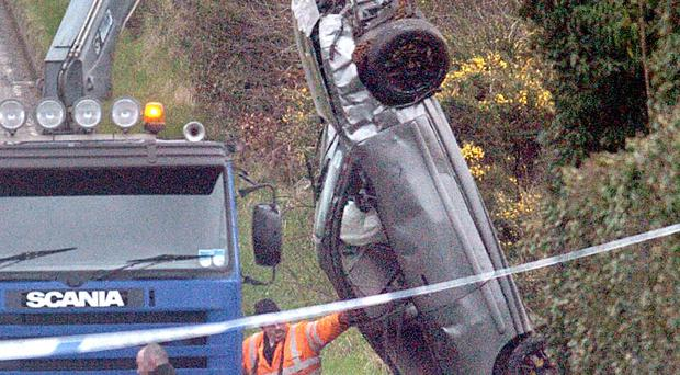 The car is winched from the side of the road after the crash near Ballynahinch yesterday