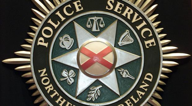 The PSNI is investigating after a woman was shot in both legs while fleeing from two masked men in Co Antrim