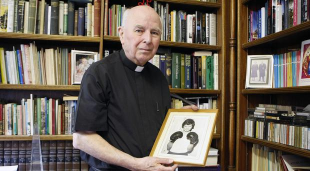 Dr Edward Daly holds a portrait of Jackie Duddy, who was shot dead in the Bogside area of Derry on Bloody Sunday
